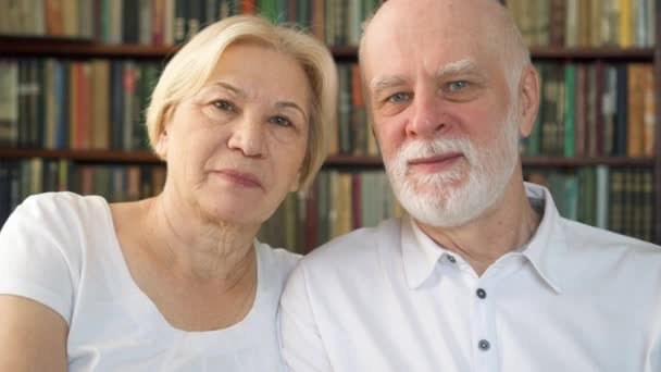 Portrait of cheerful good-looking senior couple sitting on sofa at home. Having good time relaxing.