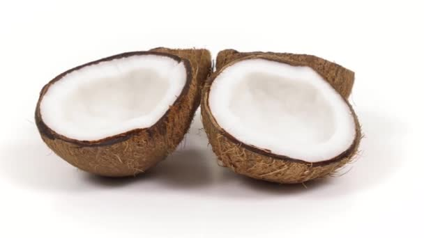 Four ripe coconut halves with yummy pulp rotating on white isolated background. Loopable seamless