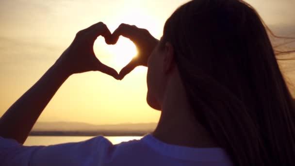 Silhouette einer jungen Frau zur goldenen Stunde in Zeitlupe, die Sonne in herzförmigen gefalteten Händen fängt