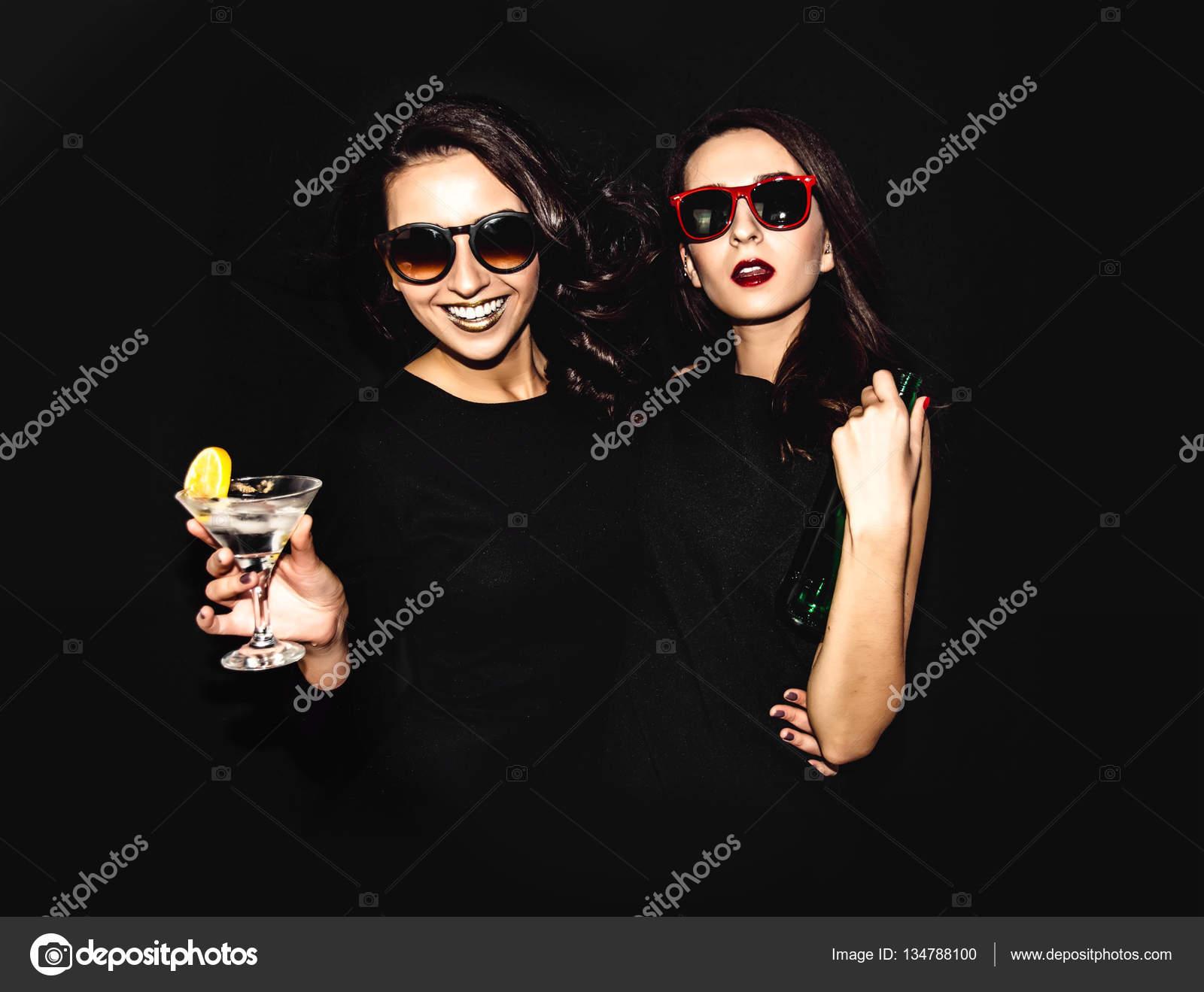 a91322faf2 Due belle donne in nero notte moda vestito in posa isolato su sfondo ...