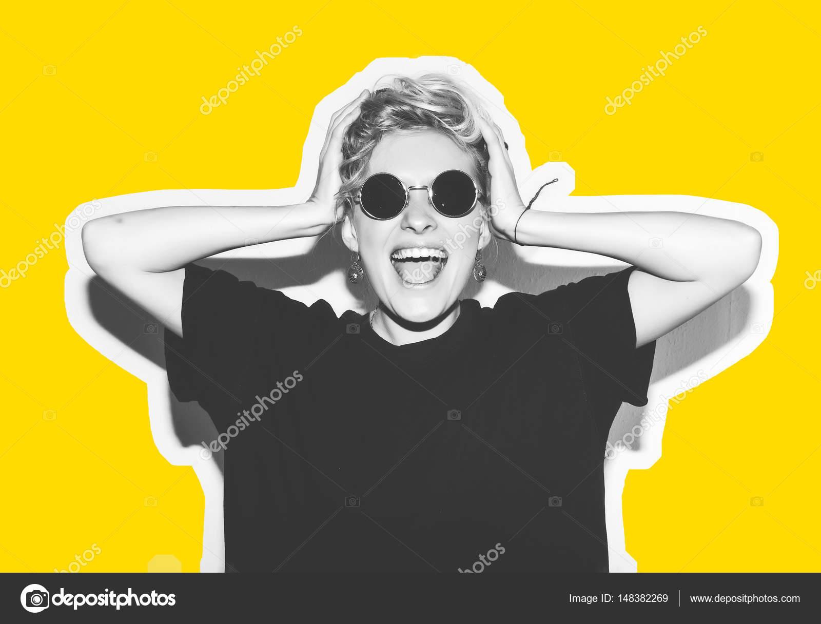 1d599e53 Rubia de moda elegante con collage de colores de pelo corto. Niña loca en  un negro camiseta y roca gafas de sol grito sosteniendo su cabeza.