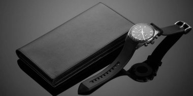Fashionable leather men's wallet and watch on a black background