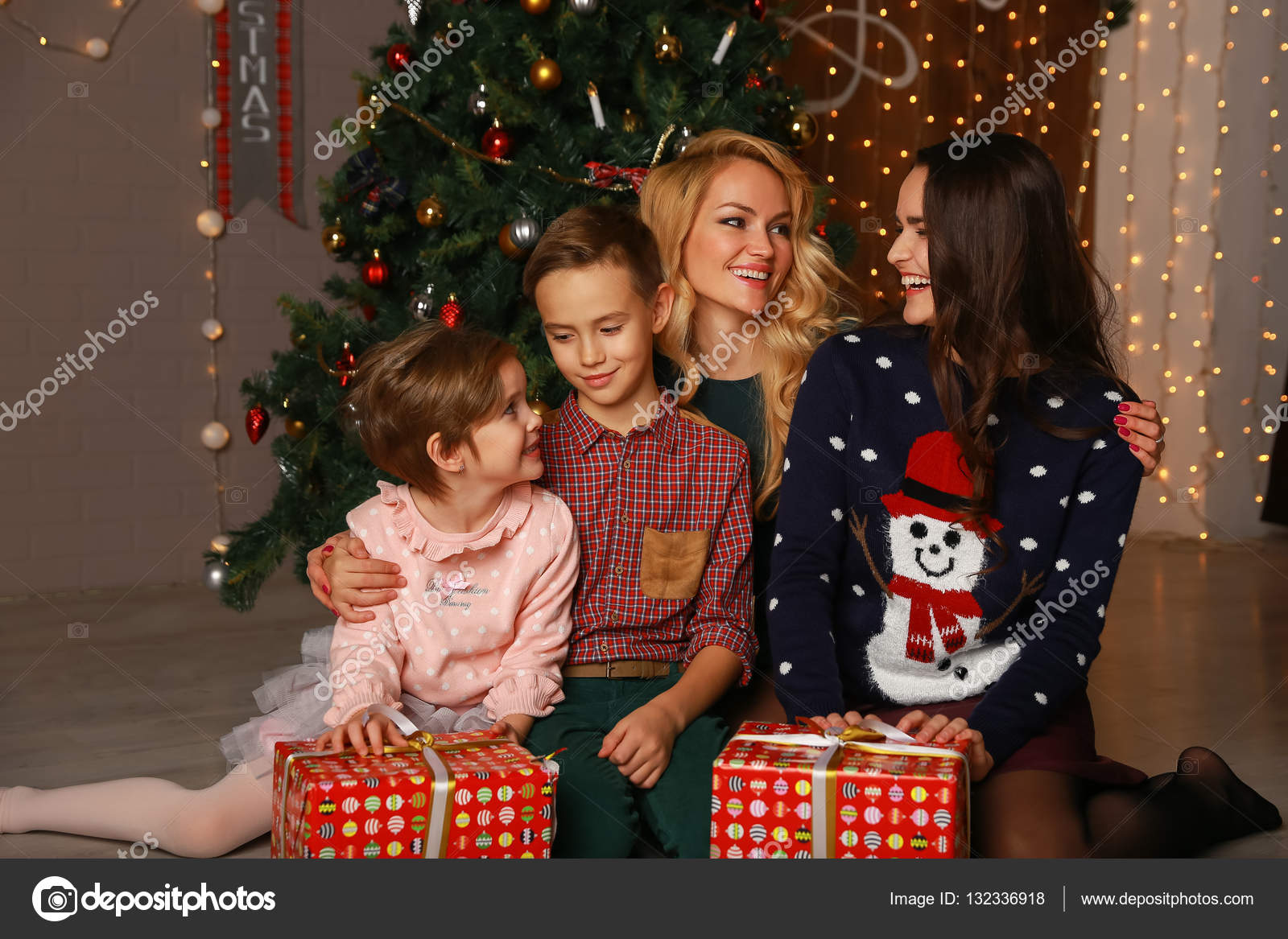 Happy Parents And Children Sharing Christmas Hugs Looking At