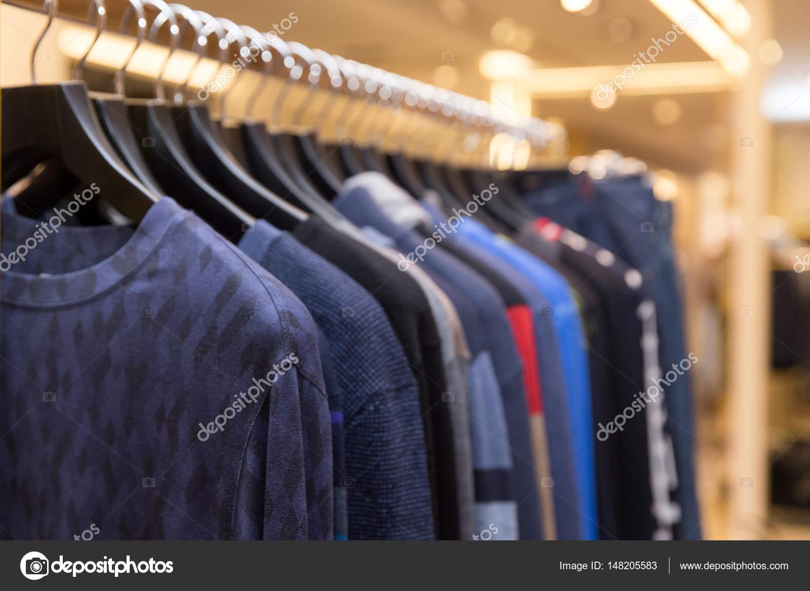 13694488502ed Erkek kazak ve gömlek askıları bir perakende giyim mağaza üzerinde farklı  renklerde. Kış sonbahar sezonu için güzel giysiler.