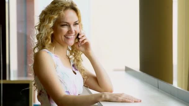 Portrét krásné ženy s zářivým úsměvem mluvit na telefonu v kavárně