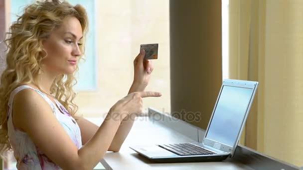 schöne Frau mit Kreditkarte in der Hand und zeigt seinen Finger auf dem Notizbuch