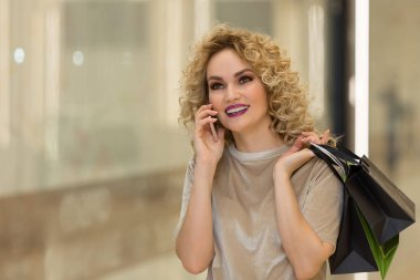 "Картина, постер, плакат, фотообои ""Beautiful woman talking on the phone with bags at the shopping mall"", артикул 155731280"