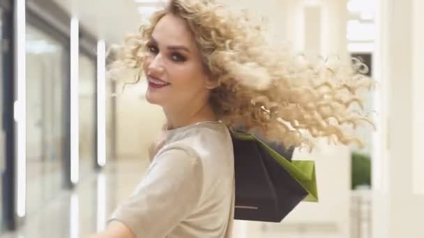 Beautiful woman turning around with shopping bags in mall, slow motion. happy girl with their purchases.