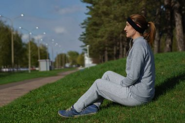 Fitness woman with smartphone sitting and listening music at city park