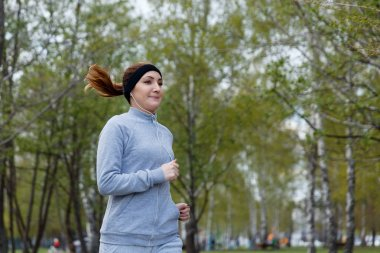 Power walking woman training in park. Beautiful sporty fitness model during outdoor workout.