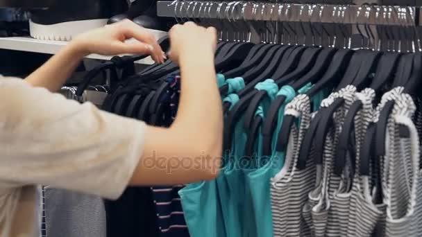 Nákupní ženy výběr oblečení v obchoďáku nebo obchod s oblečením