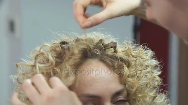 Szép, szőke hajú lány, hosszú haj, fodrász teszi afrikai fürtök szépségszalon. Professzionális hajápolás és frizura létrehozása.