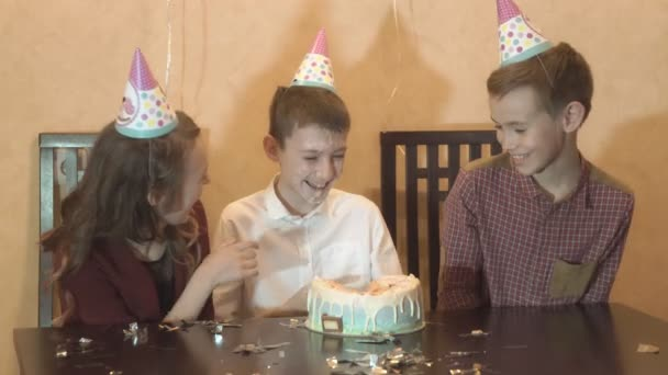 children goofing around and having fun at a birthday party. boy face smashing cake