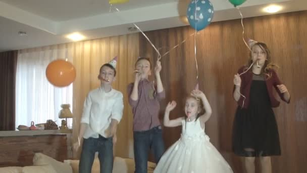 I bambini si divertono per festeggiare un compleanno. Un gruppo di bambini che saltano, danza e sorride per bambini party. Slow motion