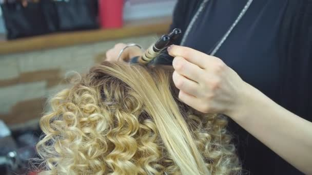 Krásné, blond vlasy dívka s dlouhými vlasy, kadeřník dělá africké kadeře v salonu krásy. Profesionální vlasová kosmetika a vytváření účesů.