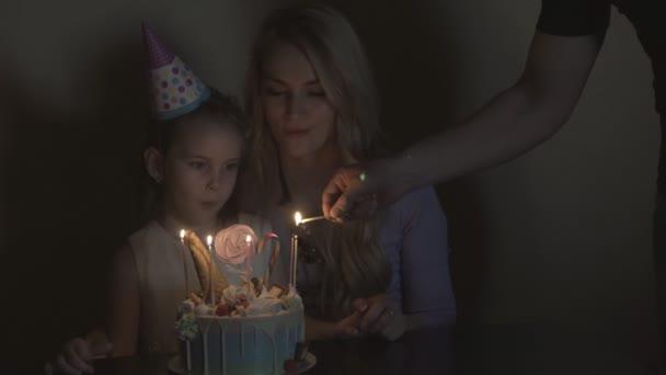 Večírek k narozeninám dítěte. Rodiče světlo svíčky na slavnostní dort. Oslavenkyně v slavnostní zakončení