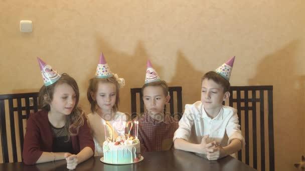 a kis szülinapos és barátai, az ünnepi asztalra. gyermekek elfújni a gyertyákat egy születésnapi torta. gyermekek születésnapi party
