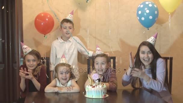 bambini che celebrano compleanno a casa. il ragazzo di compleanno e i suoi amici, ridere e divertirsi. torta di compleanno in una festa di famiglia. rallentatore