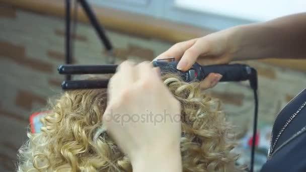 Elegán vlnitými vlasy pro blondy ženu. Dívka péče o její účes. Kadeřník dělá africké kadeře v salonu krásy