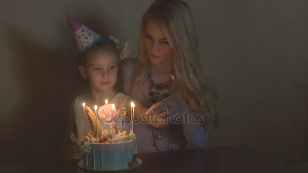 mother and daughter blow out candles on a birthday cake. the birthday of a little girl. the birthday girl in a festive hat at a childrens party