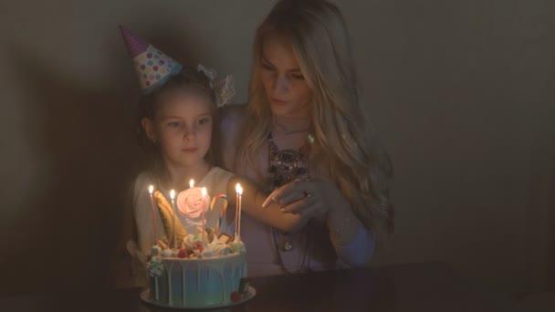 matka a dcera sfouknout svíčky na narozeninový dort. narozeniny malé holčičky. Oslavenkyně v slavnostní klobouk na dětské párty