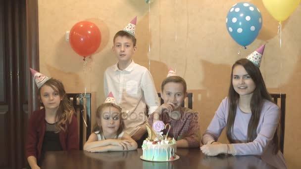 gyermekek ünnepli születésnapját otthon. a születésnapi fiú és barátai nevetés és szórakozás. születésnapi torta egy családi Party.