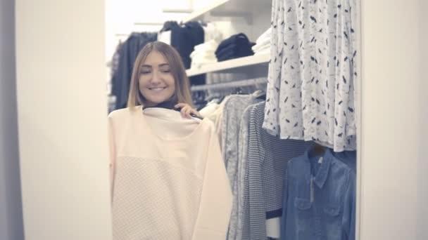 Yong dívka výběr oblečení a při pohledu do zrcadla v obchoďáku nebo obchod s oblečením
