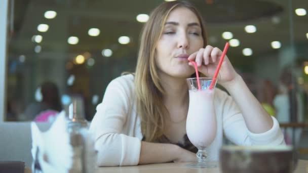 krásná mladá dívka nápoje mléko koktejl v kavárně