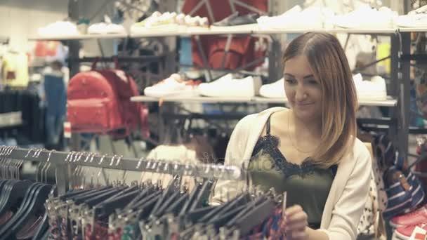 Mladé krásné ženy nakupovat v módní mall, výběr nové oblečení