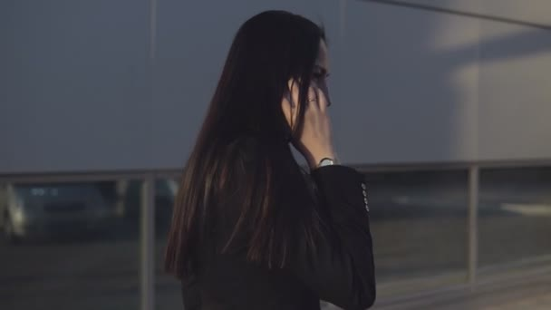 Side view - young businesswoman in black suit talking on smartphone on sunny day against the backdrop of office center outdoor