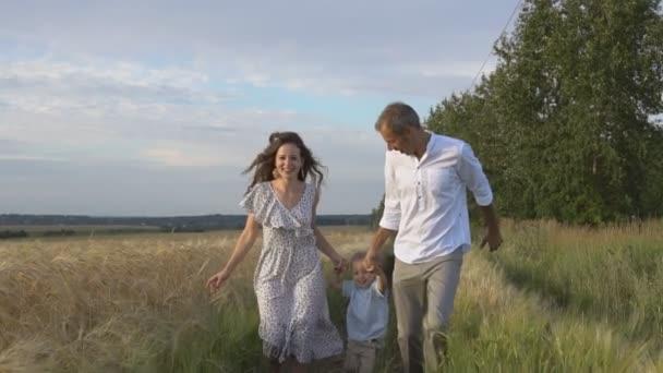 Mutter, Vater und kleiner Sohn vergnügen sich gemeinsam im Freien. Glückliche Familie rennt vor die Kamera, Zeitlupe.
