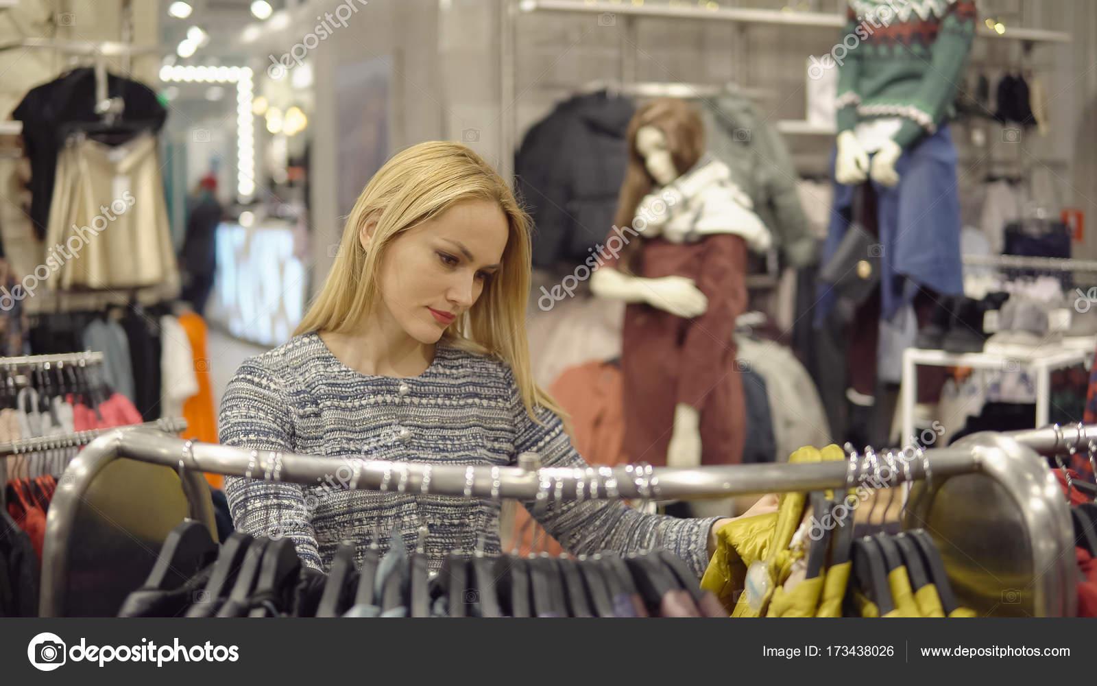 7baafaee5c6c0 Giyim, dolap, moda, stil ve insanlar kavramı - mutlu sarışın kadın giyim  mağaza seçimi– stok imaj
