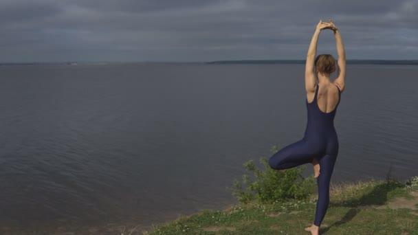 Yoga woman in sportswear against lake, back view