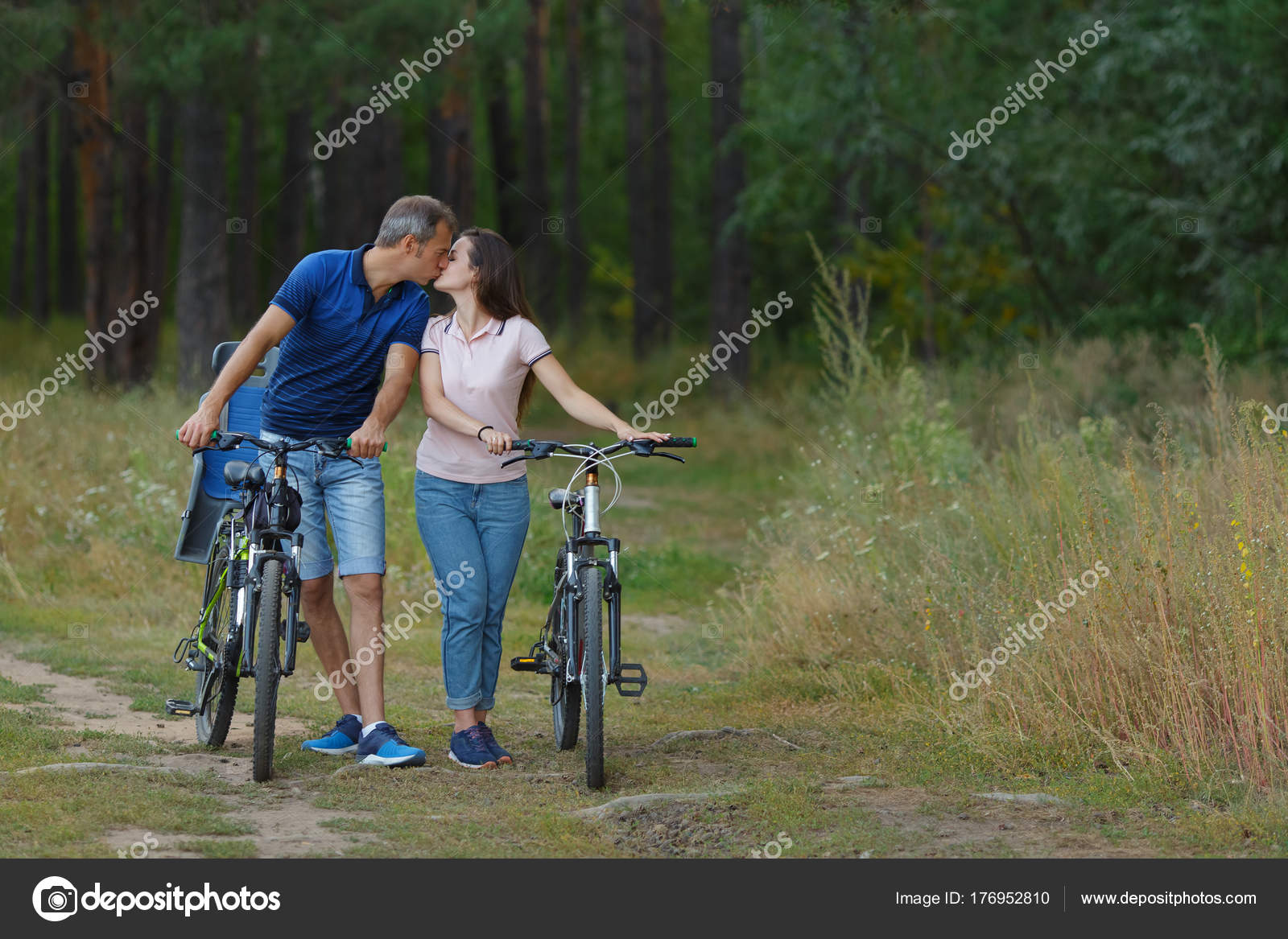 Couple Kissing In Forest Romantic Walk On Bikes Stock Photo