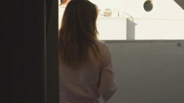 Beautiful girl in bathrobe goes to the balcony of her room at the hotel and enjoys coffee.