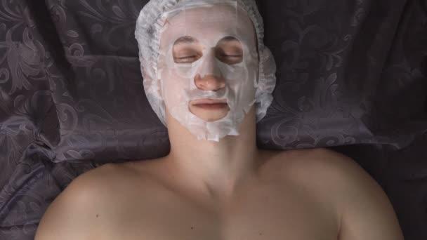 Mladý muž v salonu krásy na postupu s hydratační maska na obličej