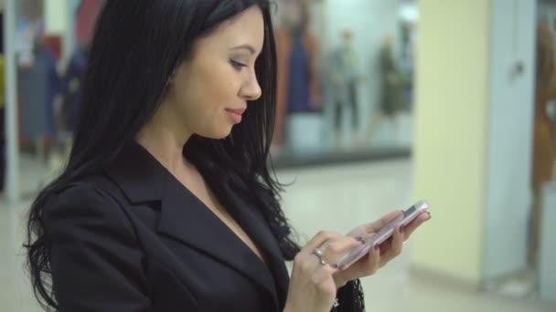 Hezká žena drží nákupní tašky a pomocí chytrého telefonu v obchoďáku
