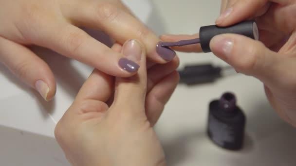 Detail použití gel lak na nehty mladé ženy v salonu krásy