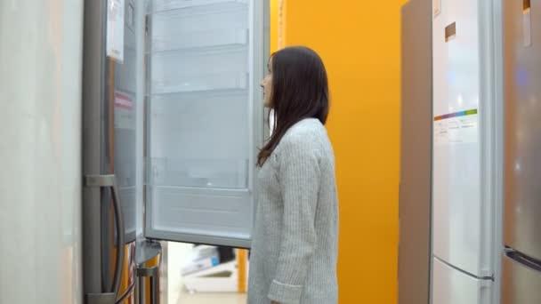 Mladá žena v obchodě domácí spotřebič zvolí chladničku