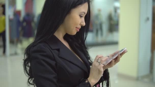Csinos nő gazdaság bevásárló táskák, és használ egy okos telefon, Mall.
