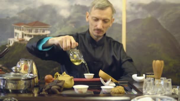 Tea ceremony. Master man pours green tea from a glass teapot into a white mug