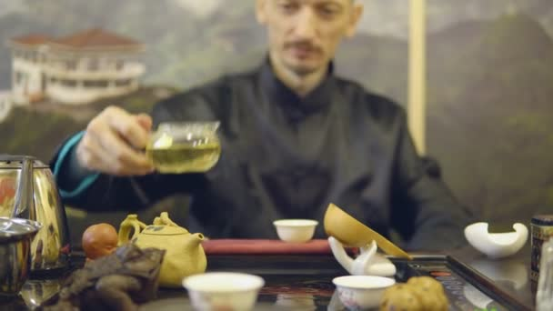Master man pours green tea from a glass teapot into a white mug