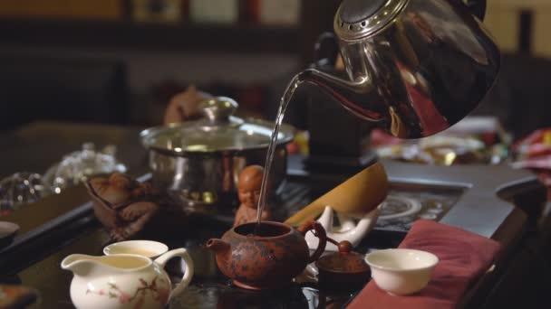 Čajový obřad. Konvice na čaj nalije vařící vodu do konvici
