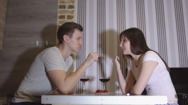 Romantický večer. Mladý pár u stolu pití vína a jíst jahody