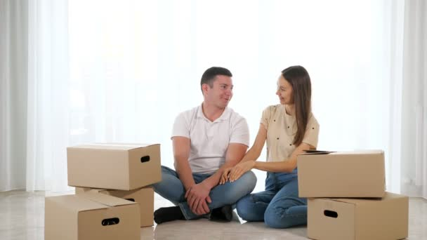 Young happy couple sitting on the floor of their new apartment among cardboard boxes