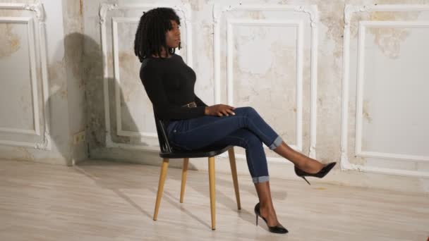exciting black lady in blue jeans sits on brown wooden chair