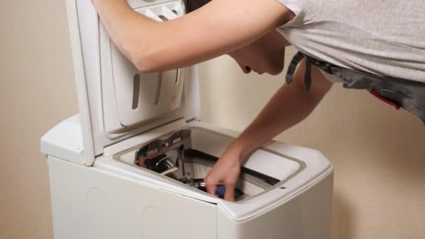 Mitarbeiter untersucht Toplader von Waschmaschine in Wandnähe