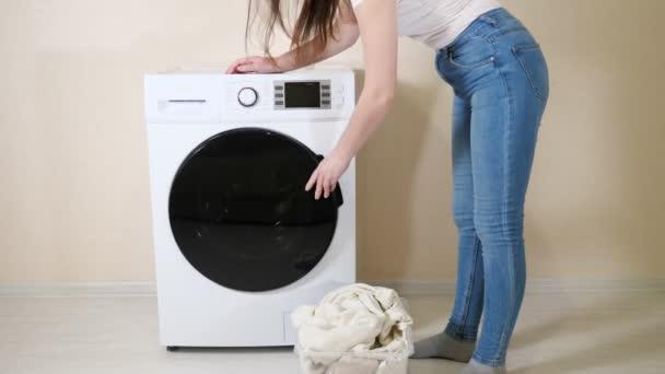 Frau lädt schmutzige Kleidung in Waschmaschine nahe beiger Wand