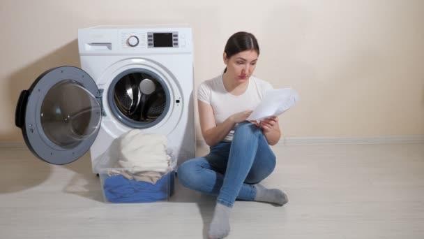Hausfrau lernt Einstellungen der neuen Waschmaschine auf dem Fußboden