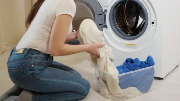 Frau lädt Kleidung im Sitzen in Waschmaschine